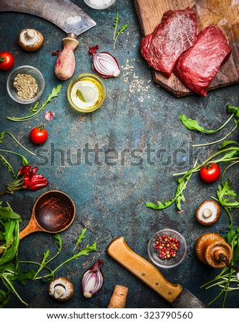 Fresh beef steak, wooden spoon, knife and aromatic herbs, spices and vegetables for cooking , on rustic background, top view, frame. - stock photo