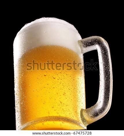 Fresh beer glass on black background. - stock photo