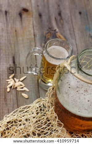 Fresh beer in a glass and in a glass jar on a wooden simple surface. Soviet still life with a glass jar of beer in a string-bag.