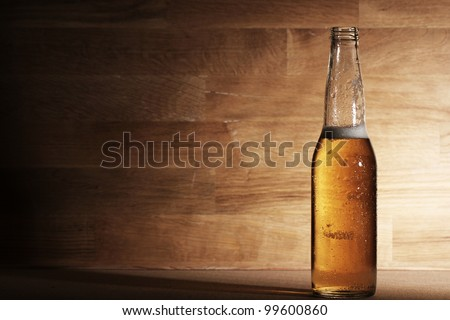 Fresh beer over wooden surface - stock photo
