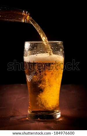 fresh beer pouring from bottle into glass on wood table - stock photo