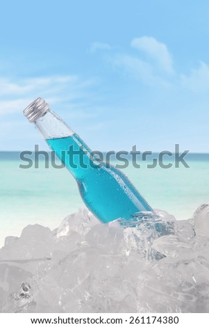 Fresh beer with blue color on the bottle in the ice cube, shot at beach - stock photo