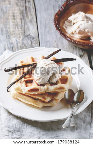 Fresh belgian waffles and bowl of ice cream, served with vanilla sticks over wooden table. See series - stock photo