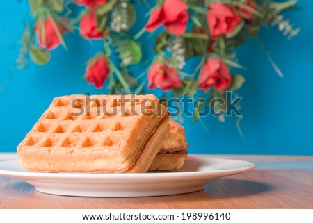 Fresh belgian waffles served on wooden tabledesk with flowers on background - stock photo