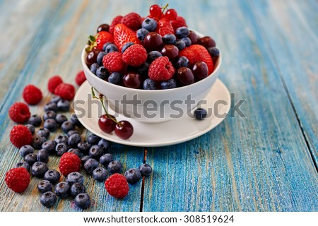 Fresh berries are heaped in a deep dish - stock photo
