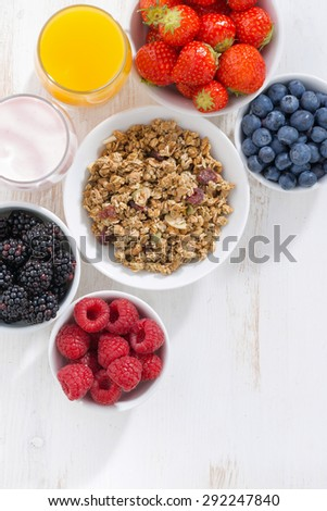 fresh berries, granola, juice and yogurt on a white wooden background, top view - stock photo