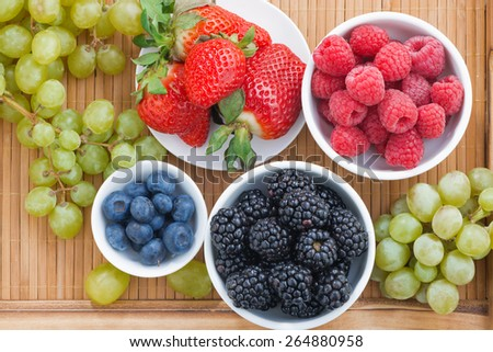 fresh berries in a bowl and green grapes on wooden tray, top view, horizontal - stock photo