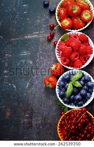 Fresh Berries on Wooden Background. Strawberries, Raspberries and Blueberries. Health, Diet, Gardening, Harvest Concept - stock photo