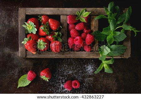 Fresh berries strawberry and raspberry with bunch of mint in old wooden sectioned box over dark textured background. Top view. With copy space