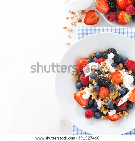 fresh berries, yogurt and granola for breakfast and space for text, top view - stock photo