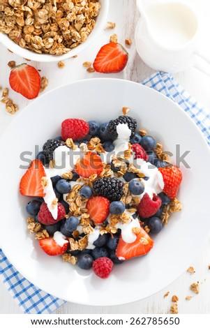 fresh berries, yogurt and muesli for breakfast close-up, vertical, top view - stock photo