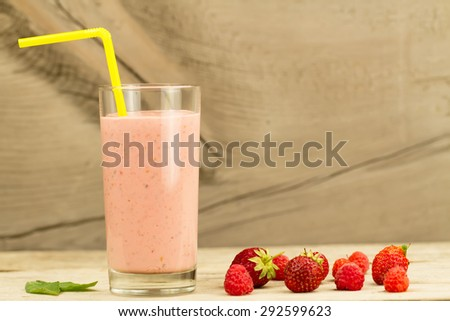 fresh berry smoothie with raspberries and strawberries on wooden background