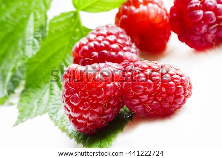 Fresh big raspberry with leaves on a white wooden background, not isolated, a macro shot, selective focus