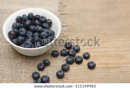 Fresh bilberries in a bowl on a wooden table