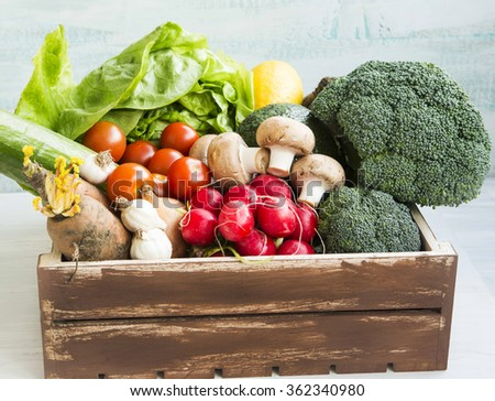 Fresh bio vegetables in wooden crate with salad,carrots,mushrooms,tomatoes,broccoli,radish,avocado,onions and garlic - stock photo