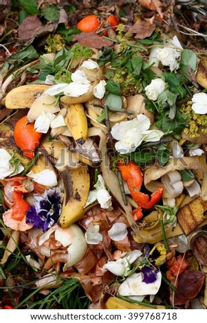 Fresh bio-waste and compost in the garden with white roses - stock photo
