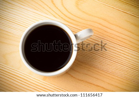 Fresh Black Coffee in a White Ceramic Cup on a Wooden Table