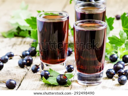 Fresh black currant juice with berries in glasses on an old wooden table, selective focus - stock photo