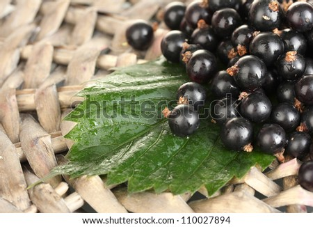 Fresh black currant on wicker mat close-up - stock photo
