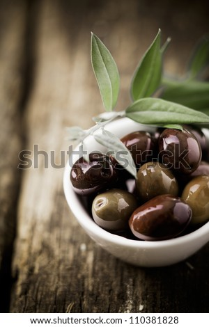 Fresh black olives in a bowl for appetizers to be served with drinks before a meal with copyspace - stock photo
