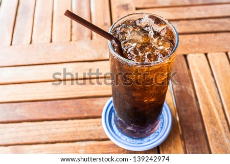 Fresh black soda with ice on wood table - stock photo