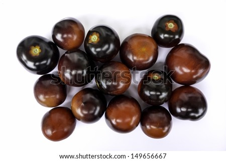 Fresh black tomatoes presented on a white background