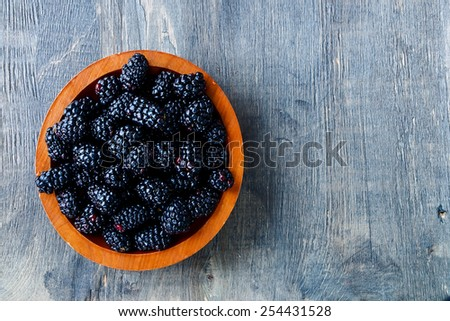 Fresh blackberries in wooden bowl. Top view. - stock photo