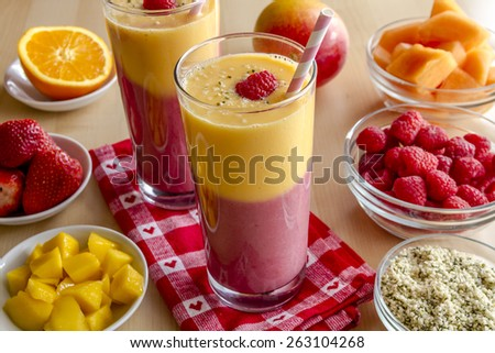 Fresh blended fruit smoothies made with mango, orange, cantaloupe, raspberries, strawberries and hemp seeds surrounded by raw ingredients with pink swirled straws and red heart napkin - stock photo