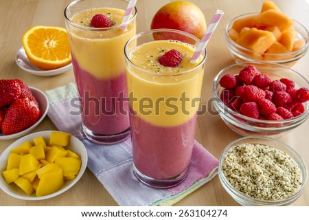 Fresh blended fruit smoothies made with mango, orange, cantaloupe, raspberries, strawberries and hemp seeds surrounded by raw ingredients with pink swirled straws and pastel napkin - stock photo