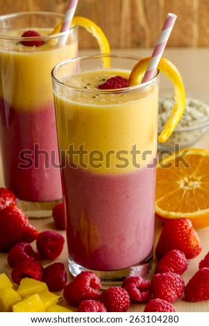 Fresh blended fruit smoothies made with mango, orange, cantaloupe, raspberries, strawberries and hemp seeds surrounded by raw ingredients with pink swirled straws - stock photo