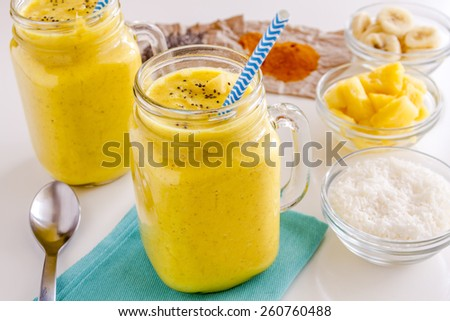 Fresh blended fruit smoothies made with pineapple, banana, coconut, turmeric and chia seeds surrounded by raw ingredients with blue straws - stock photo