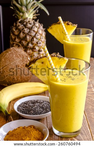Fresh blended fruit smoothies made with pineapple, banana, coconut, turmeric and chia seeds surrounded by raw ingredients in drinking glass with pineapple slice garnish and yellow swirled straw - stock photo