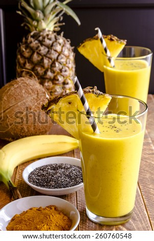 Fresh blended fruit smoothies made with pineapple, banana, coconut, turmeric and chia seeds surrounded by raw ingredients in drinking glass with pineapple slice garnish and blue swirled straw - stock photo