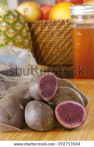 Fresh blue potatoes in plastic sack in kitchen - stock photo