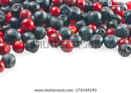 Fresh blueberries and cranberries scattered, isolated on white