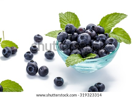 fresh blueberries and mint leaves in a glass bowl on white background - stock photo