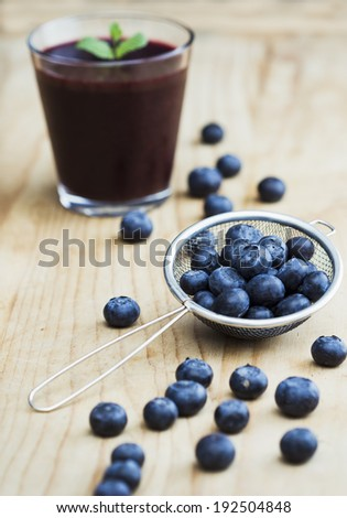 Fresh blueberries and smoothie on the table - stock photo