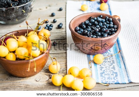 Fresh blueberries, cherries and mulberries on a gray wooden background, assorted berries, summer, rustic - stock photo