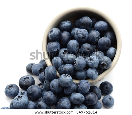 fresh blueberries falling from the cup isolated on white
