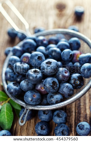 Fresh blueberries from organic cultivation on rustic wooden table, top view, close up