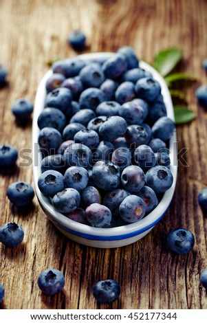 Fresh blueberries in an oval ceramic pot on a wooden table