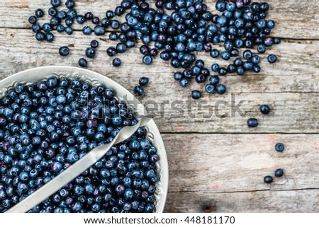 Fresh blueberries in basket on wooden table, ripe fruits from forest on farmer market, top view - stock photo