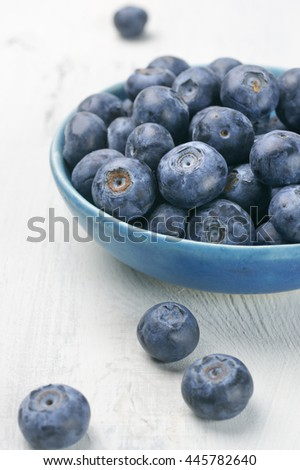 Fresh blueberries in blue bowl on white rustic wooden background.