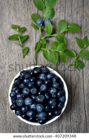 Fresh blueberries in bowl on wooden background, top view - stock photo