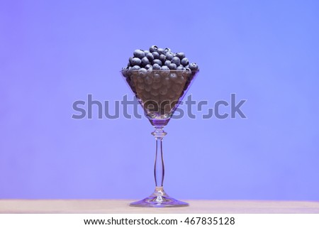 Fresh blueberries in shining conic glass on table. Copy-space. Close up. Indoor shot