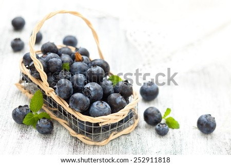 Fresh blueberries in small basket with mint .  On white wooden table. - stock photo
