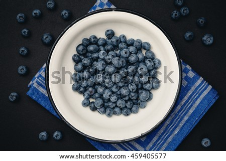 Fresh blueberries in vintage bowl on black background. Photo with shallow depth of field.