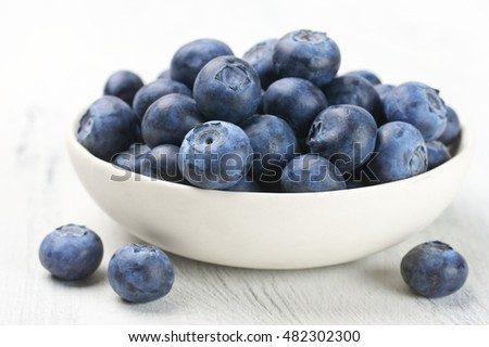 Fresh blueberries in white bowl on white rustic wooden background.