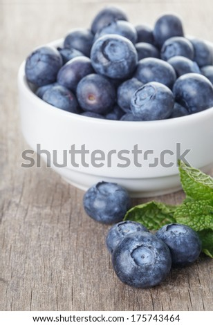 fresh blueberries in white bowl on wood table, rustic style