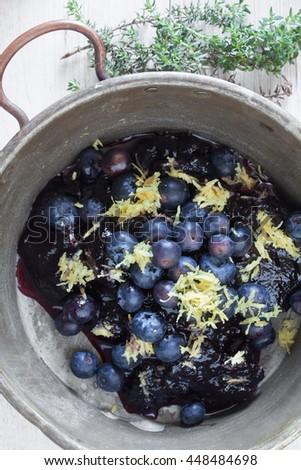 Fresh blueberries with grated lemon peel inside vintage copper pan and fresh thyme, ingredients for blueberry pancakes. - stock photo